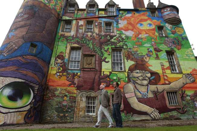 The Earl of Glasgow, Patrick Boyle (L), and his son David, the Viscount Kelburn, pose for photographers next to graffiti paintings by Brazilian artists on the walls of Kelburn Castle near Largs, Scotland August 30, 2011. Boyle, the owner of the castle, has written to Historic Scotland asking if the mural, which was completed by Brazillian graffiti artists in 2007, can be kept after the three-year time limit, which was put on the artwork by the local council, has expired. REUTERS/David Moir (BRITAIN - Tags: ENTERTAINMENT SOCIETY)